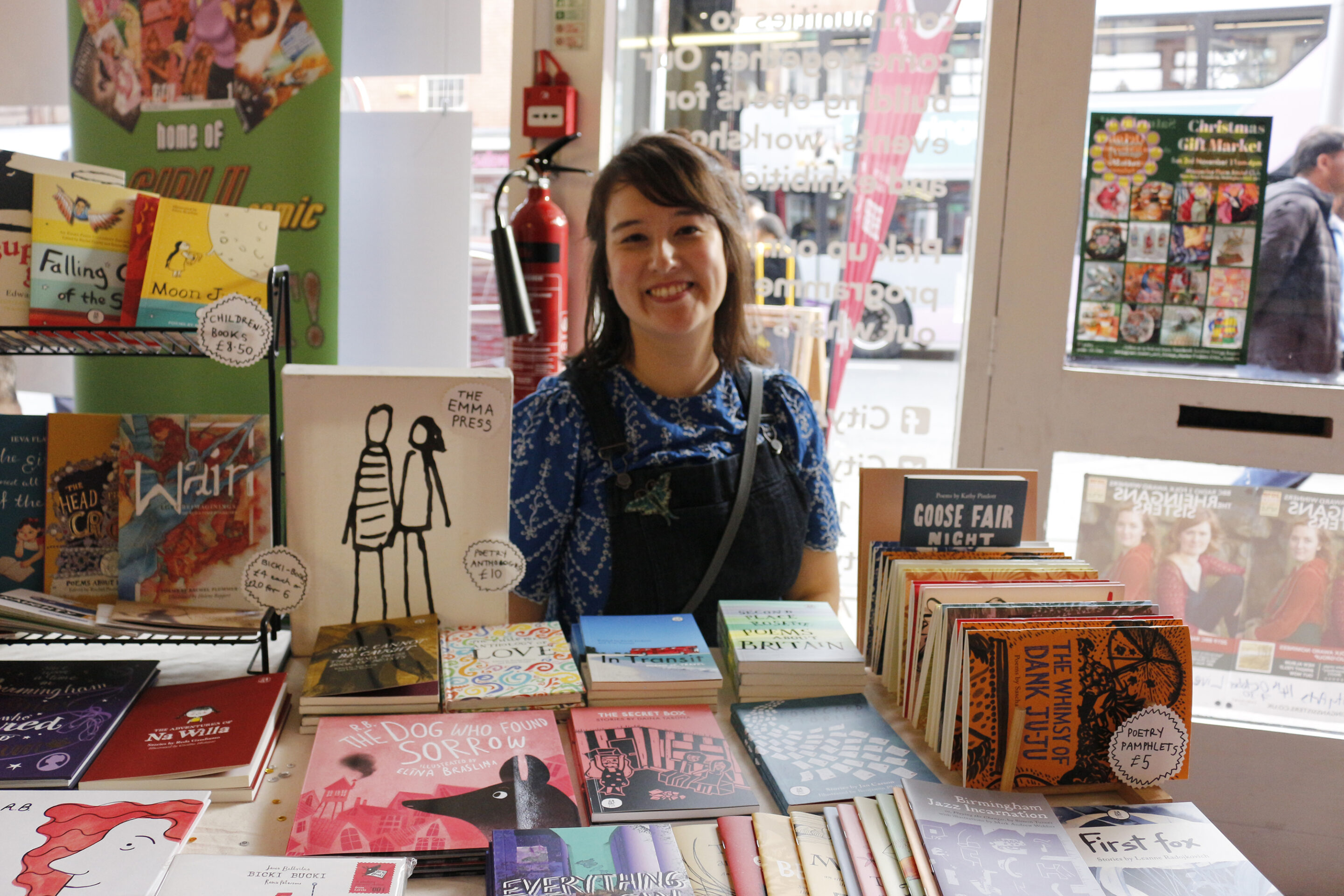Emma Dai'an Wright sitting behind a pile of books at a bookshop.